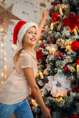 Photo of girl in Santa caps on background of New Years decorations
