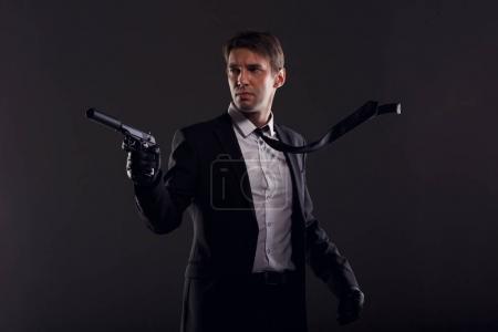 Photo pour Image de l'homme de la mafia avec cravate émergente dans les gants de cuir avec pistolet isolée sur fond noir - image libre de droit