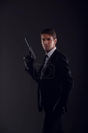 Photo pour Photo de l'homme de la mafia dans les gants de cuir avec pistolet isolée sur fond noir - image libre de droit