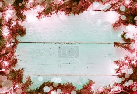 Christmas wooden bokeh background with fir tree and lighted garl