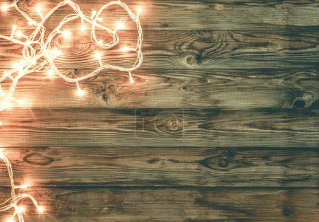 Photo for Christmas dark brown wooden background decorated with shining lights. Festive x-mas and new year template for your logo, text, and other design needs. Top view - Royalty Free Image