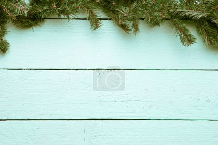 Spruce branch on white wooden surface. New year, Christmas backg