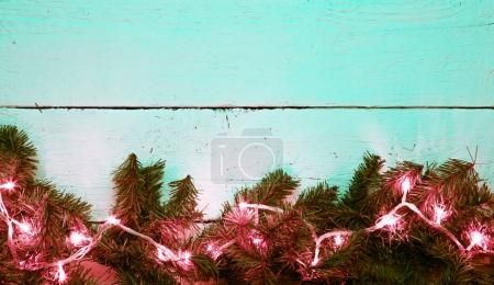Christmas lighted fir tree over wooden background with copyspace