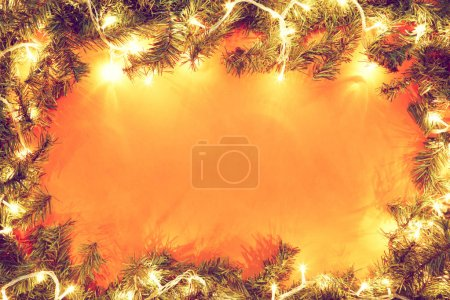 Photo for Christmas fir branches with garlands on orange background - Royalty Free Image