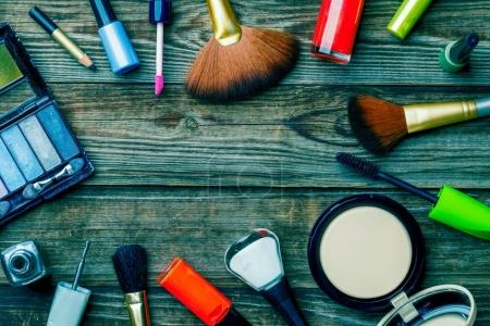 Makeup cosmetics, brushes and other on brown background