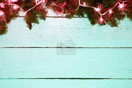 Christmas holiday wooden background with fir tree and golden gar