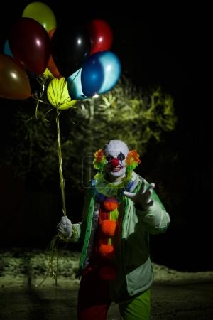 Photo of smiling clown with colorful balloons at night