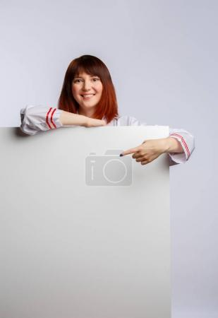 Image of chef girl in white lab coat with empty sheet for inscription
