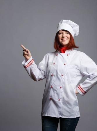 Image of smiling brunette chef in white robe pointing finger at empty space