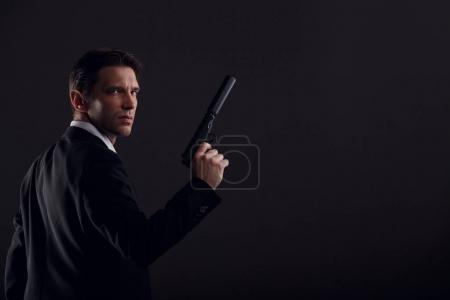 Photo pour Image de l'arrière de l'homme gangster avec pistolet isolée sur fond noir - image libre de droit