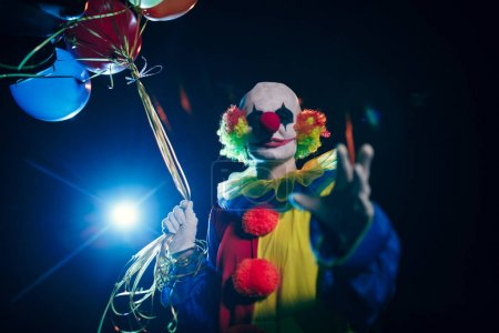 Picture of smiling clown with balloons against background of burning lantern