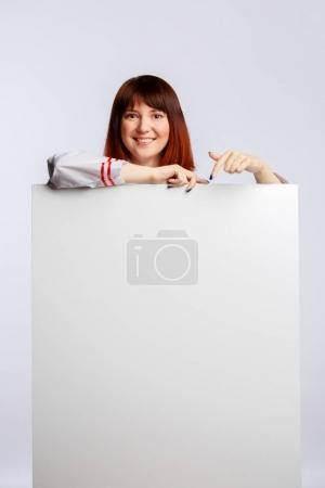 Picture of brunette cook in white coat with empty poster