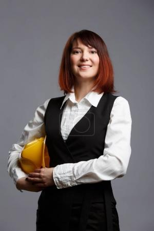 Photo for Photo of woman builder with yellow helmet on empty gray background - Royalty Free Image
