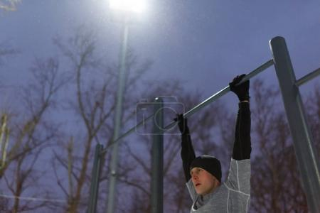 Photo of athlete pulling on bar in evening