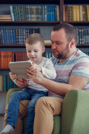 Picture of father and little son sitting with tablet on green chair