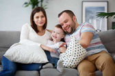 Image of happy pregnant woman, man with son on gray sofa