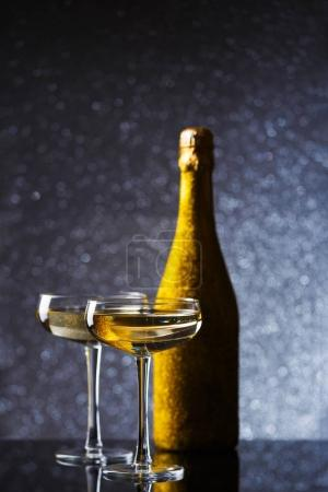 Picture of bottle of sparkling wine in gold wrapper with two wine glasses