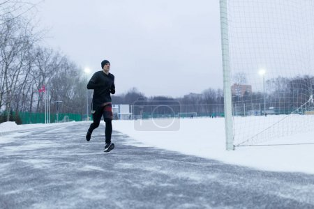 Photo for Image of sporty man running at stadium in winter evening - Royalty Free Image