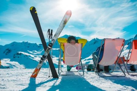 Photo from back of vacationers in armchair, skis, sticks in snowy resort