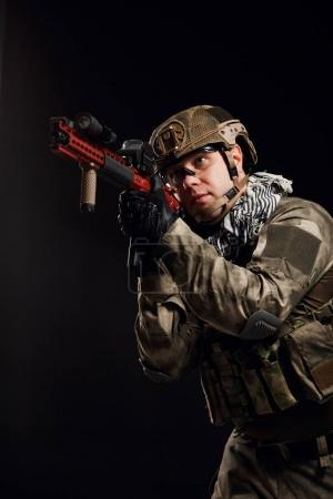 Portrait of aiming soldier with gun