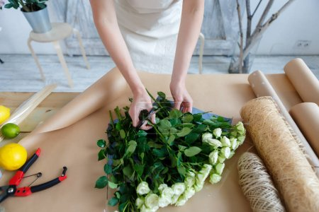 Woman makes bouquet on table