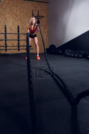 Photo for Portrait of young athlete girl in training with two ropes in gym - Royalty Free Image