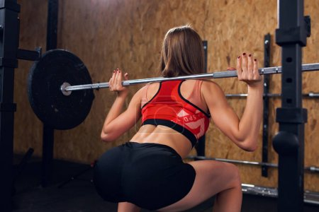 Image from back of sports woman crouching with bar