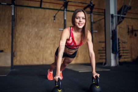 Portrait of spotswoman doing horizontal push-ups with kettlebells .
