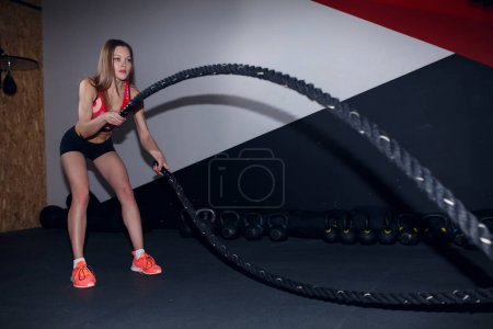 Image of female athlete in training with two black ropes