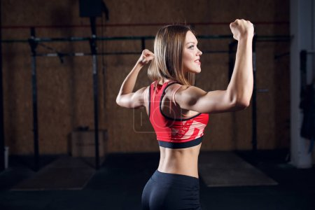 Photo for Portrait from back of sports girl showing biceps in gym - Royalty Free Image
