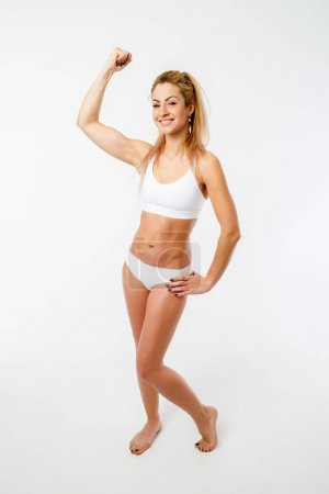 Image of woman with underwear showing biceps isolated on white background