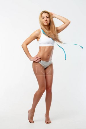 Photo of slender woman with centimeter ribbon in studio
