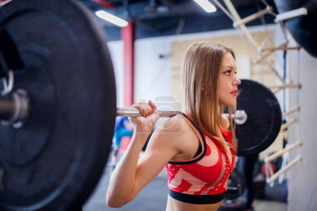 Photo of sports woman squatting with bar