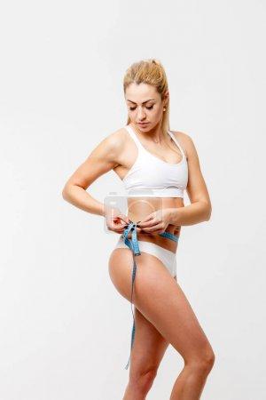 Photo of slender blonde measuring waist with centimeter ribbon in studio