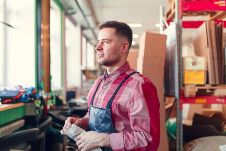 Photo of man in apron with bag in hands at shop for making coffee