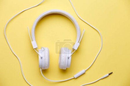 Picture of white headphones for music on yellow background