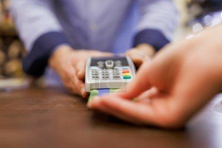 Photo pour Photo du vendeur mâle avec le terminal en main et acheteur avec carte bancaire. Arrière-plan flou. - image libre de droit