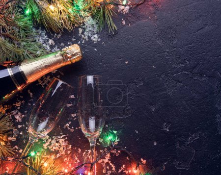 Photo for Picture of branches of fir, , burning garlands, champagne bottles, two wine glass on black background, place for text - Royalty Free Image