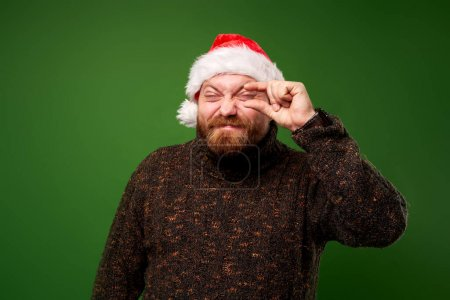 Photo for Squinted man in santa hat and sweater on empty green background in studio - Royalty Free Image