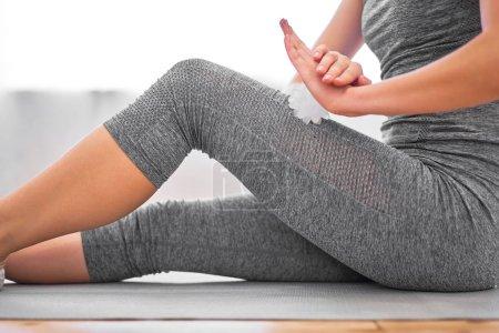 Photo pour Fille avec boule de massage dans ses mains assis sur le tapis dans la salle de gym pendant la journée - image libre de droit