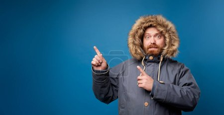 Photo for Man in winter jacket with fur on empty blue background in studio, points to empty place - Royalty Free Image