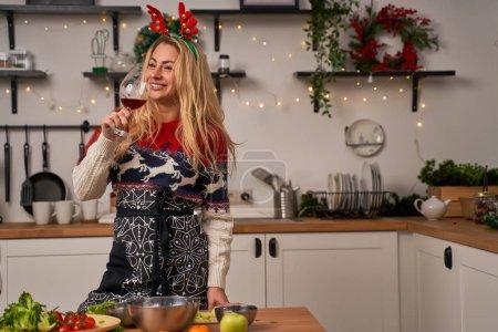 Photo pour Fille à Noël, les cornes de chevreuil boivent du vin debout dans la cuisine. Nouvelle année - image libre de droit