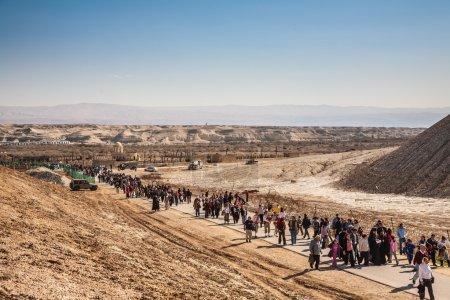 Pilgrims and tourists walking through desert