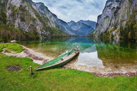 Photo pour Bateau de pêche avec petit moteur dans les eaux peu profondes du lac bleu Obersee dans les Alpes bavaroises. Concept de tourisme actif et de tourisme écologique - image libre de droit