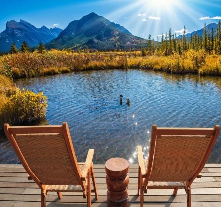 Photo pour Deux chaises longues sur plate-forme en bois sur le lac dans les montagnes Rocheuses du Canada à l'été indien, Concept de tourisme écologique - image libre de droit