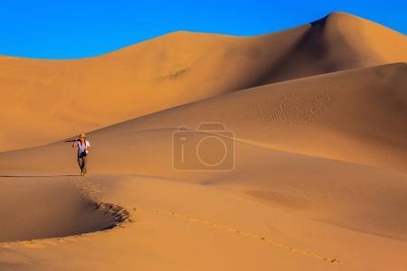 photographer walking in sand dunes