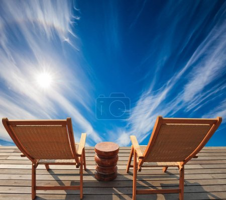 Two deckchairs in front of blue sky
