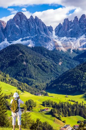 Active woman-tourist with backpack at Dolomites mountains. The concept of ecological and active tourism