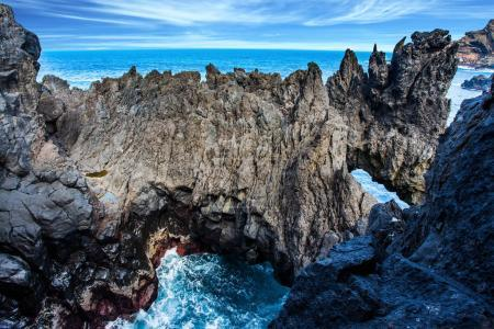 Picturesque rocks and stones at volcanic island of Madeira at coast of Atlantic. Concept of exotic and ecological tourism