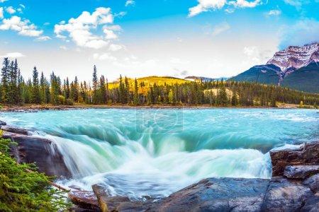 Photo pour Voyage à Jasper Park, Canada. Les eaux d'un glacier de montagne en fusion alimentent la chute d'eau en plein essor de l'Athabasca. Soirée d'automne claire au coucher du soleil. Le concept de tourisme extrême et écologique - image libre de droit